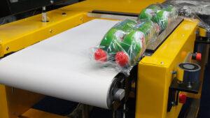 Alfatechnics hoeksealer uitloop transportband krimpverpakkingsmachine met bijhorende krimptunnel.