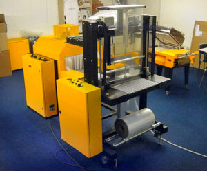 Bundel- verpakkingsmachine met manuele produkttoevoer en pneumatische lasstempel sluiting. De toevoerbaan kan ook een eenvoudige rollenbaan worden.