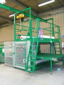 Alfatechnics Farbal folieverpakkingsmachine met krimptunnel voor het verpakken van autoruiten. Loopbrug met kettinghaspel voor het laden van de rollen folie aan de bovenzijde.
