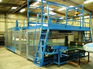 Farbal bundelverpakkingsmachine met krilmptunnel voor industriele verpakkingen van grote en zware producten op stapels.