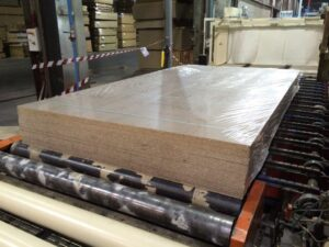 Alfatechnics Farbal Krimptunnel en krimpverpakkingsmachine voor stapels MDF platen in quasi volledig gesloten folieverpakking met PE folie.