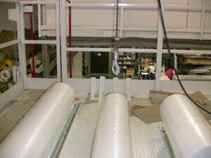 Alfatechnics Farbal multi-breedte krimpverpakkingsautomaat bovenste foliehouders met loopvlak tusen de rollen.